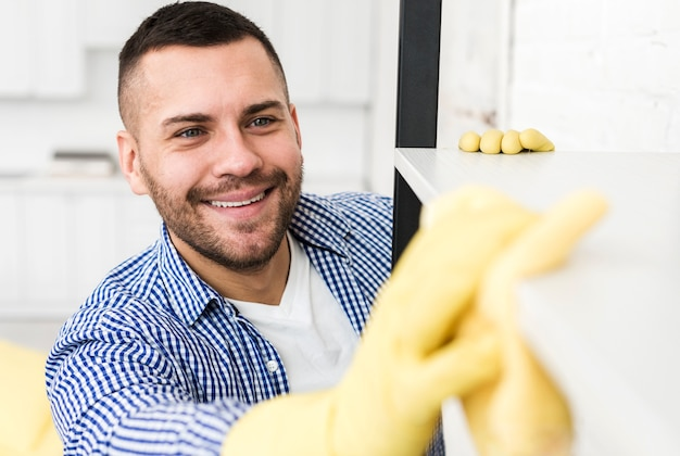 Smiley man using rag to clean