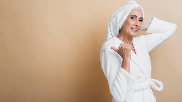 Smiley mature femme en peignoir posant