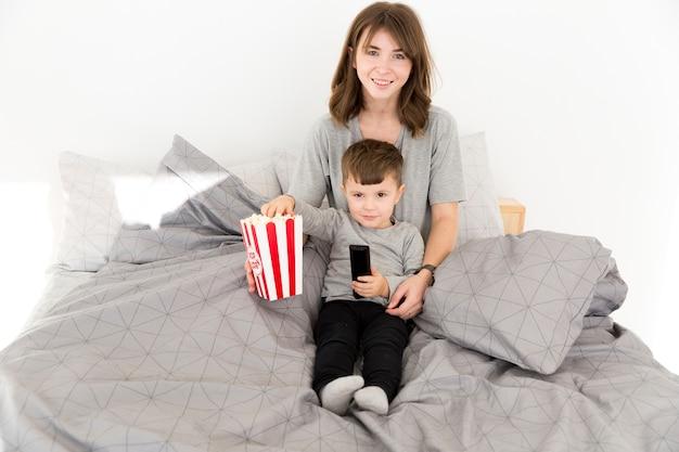 Smiley mère et fils partageant du pop-corn