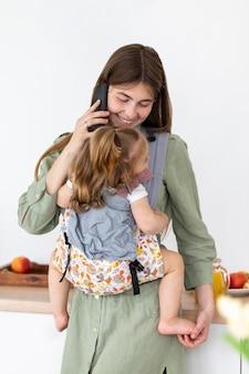 Smiley mère avec téléphone tenant une fille