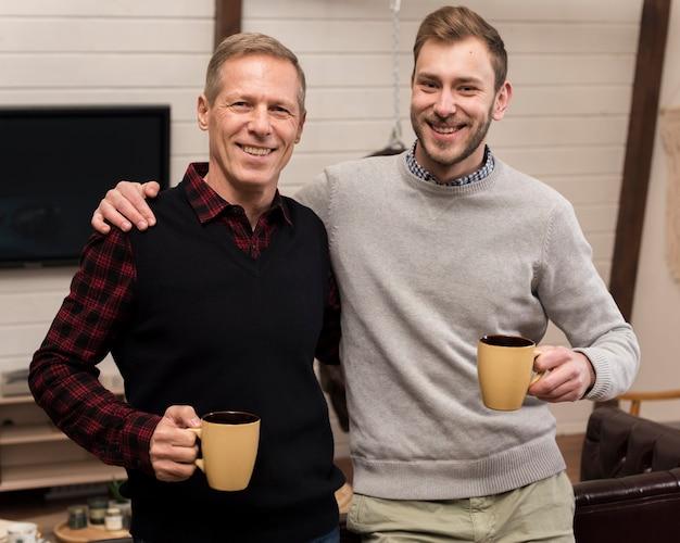 Smiley père et fils posant tout en tenant des tasses