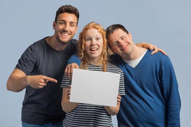 Smiley personnes posant tandis que femme tenant une carte vide