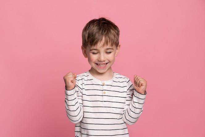 Smiley petit garçon isolé sur rose