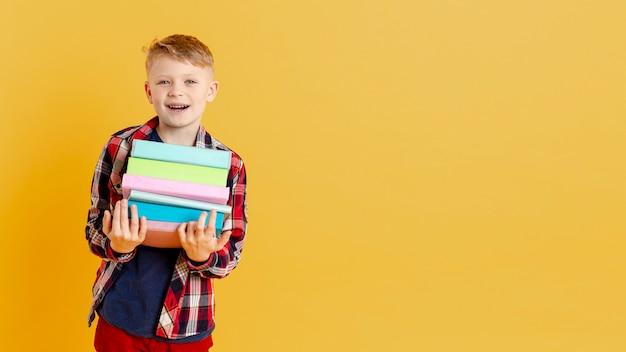 Smiley petit garçon avec une pile de livres