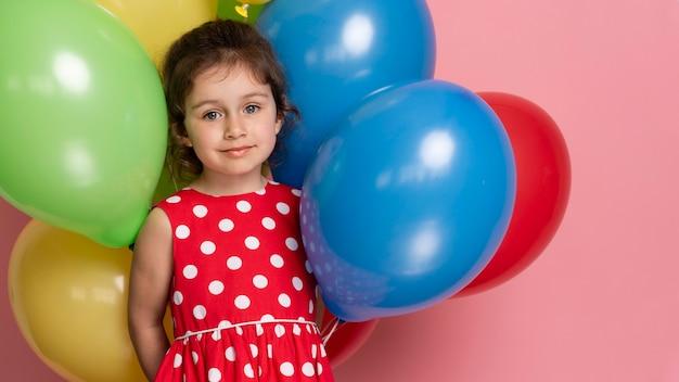 Smiley petite fille dans une robe rouge célébrant son anniversaire