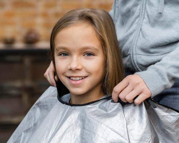 Smiley petite fille lors d'un rendez-vous avec son coiffeur