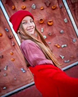 Smiley petite fille posant à côté d'un mur d'escalade