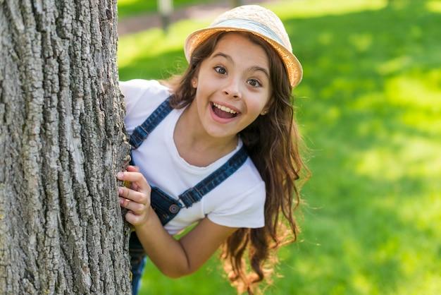 Smiley petite fille posant derrière un arbre