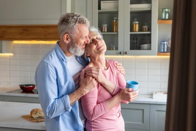 Smiley senior couple dans la cuisine coup moyen