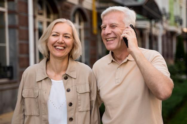 Smiley senior couple à l'extérieur tout en prenant sur smartphone