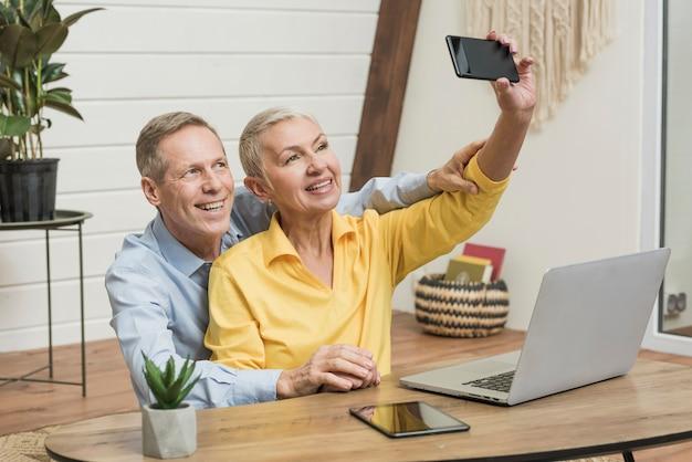 Smiley senior couple prenant un selfie