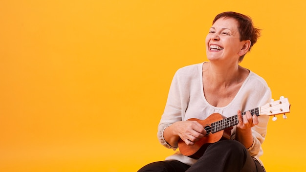 Smiley senior femme jouant de la guitare