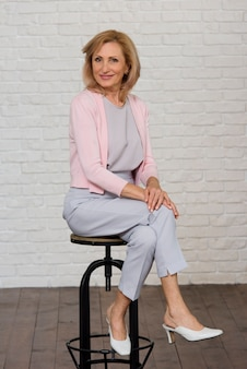 Smiley senior femme posant sur une chaise noire