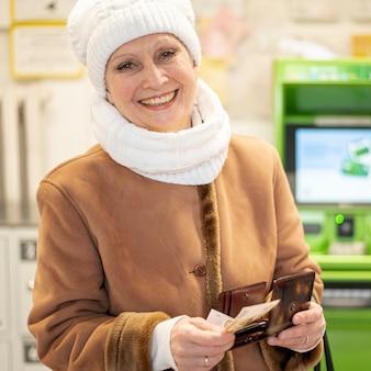Smiley senior femme prend de l'argent du portefeuille