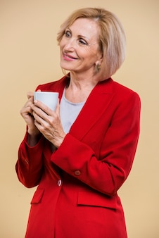Smiley senior femme à la recherche de suite tout en tenant une tasse de café