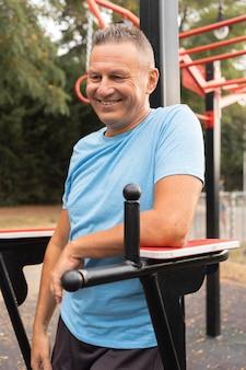 Smiley senior man posant tout en travaillant à l'extérieur
