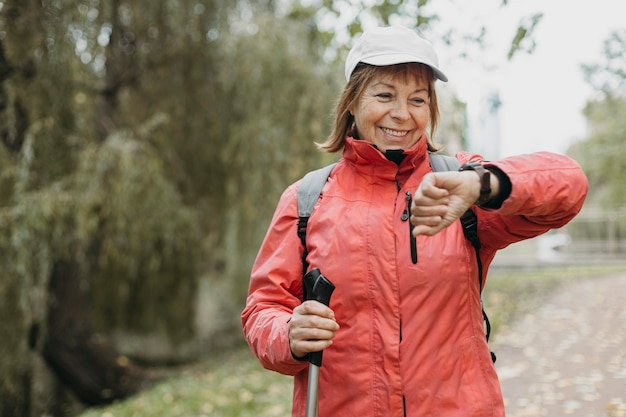 Smiley senior woman avec bâtons de randonnée à l'extérieur en regardant sa montre