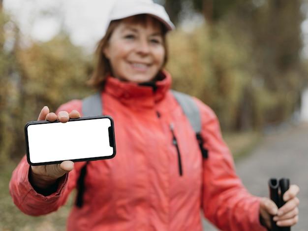 Smiley senior woman avec bâtons de randonnée tenant le smartphone à l'extérieur