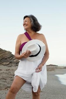Smiley senior woman à la plage profitant de sa journée