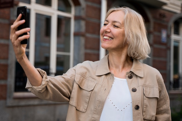 Smiley senior woman prenant un selfie en ville
