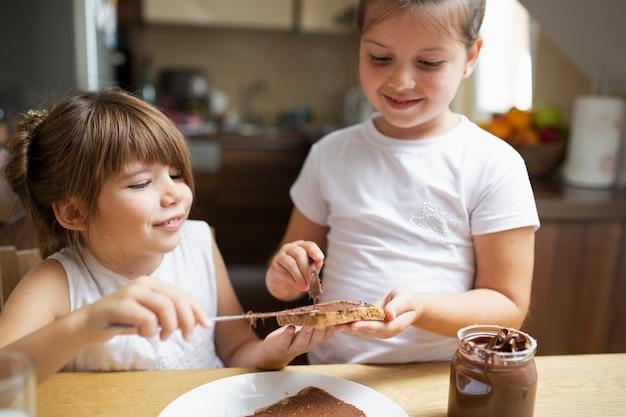 Smiley sœurs partageant le petit déjeuner ensemble