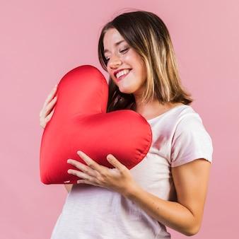 Smiley tenant un oreiller en forme de coeur