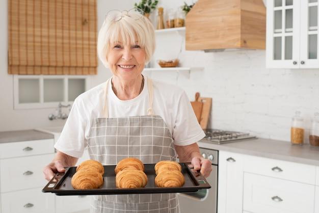 Smiley vieille femme tenant un plateau avec des croissants