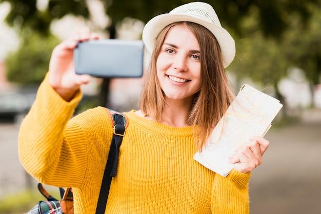 Smiley voyageant femme prenant un selfie
