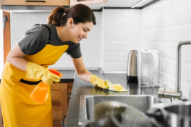 Smiley woman cleaning kitchen