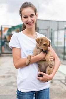 Smiley woman holding adorable chien de sauvetage au refuge d'adoption