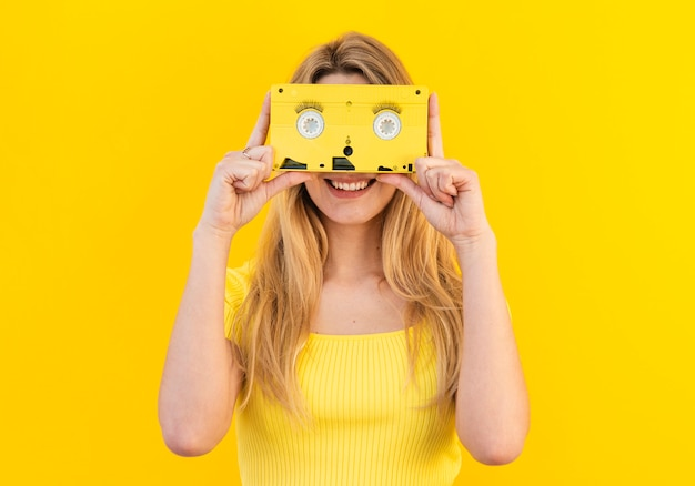 Smiley woman holding cassette
