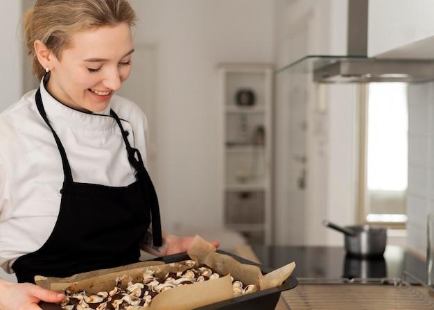 Smiley woman holding plateau avec dessert