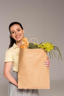 Smiley woman holding sac en papier avec des légumes