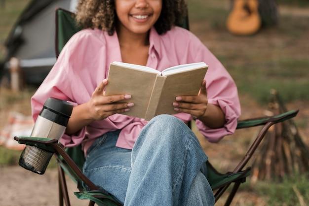 Smiley woman reading book en camping en plein air