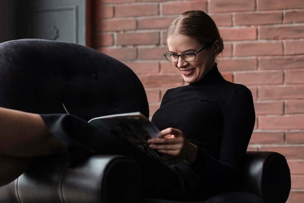 Smiley woman reading magazine
