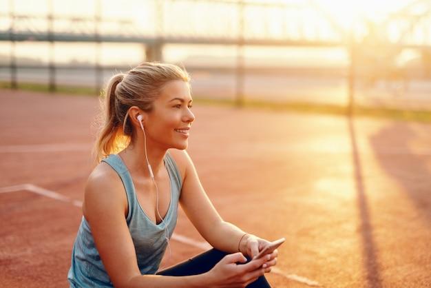 Smiling blonde caucasian woman sitting on the court avec des écouteurs dans les oreilles et un téléphone intelligent dans les mains le matin.