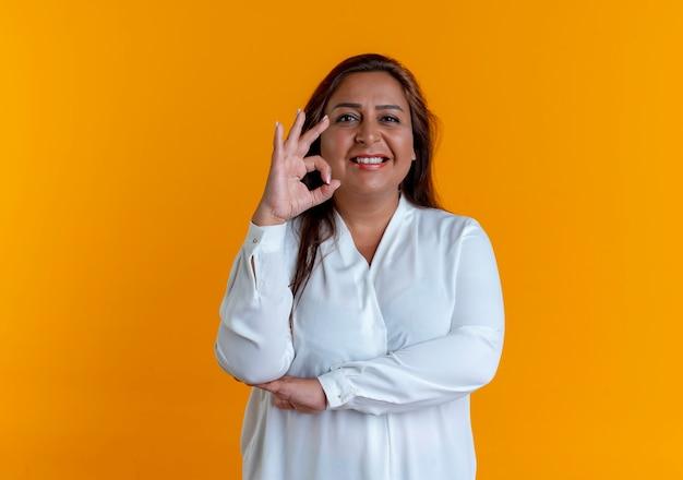Smiling casual caucasian femme d'âge moyen montrant le geste okey isolé sur mur jaune