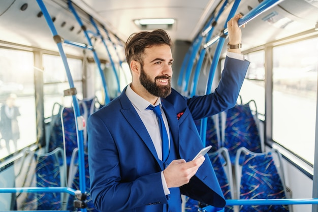 Smiling caucasian businessman in formal wear standing in public bus, holding bar and using smart phone.