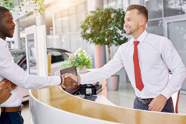 Smiling caucasian sales expert accueillant les clients dans la salle d'exposition de voiture