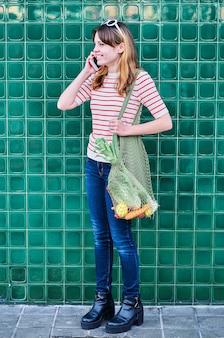 Smiling caucasian young girl talking sur le téléphone mobile avec un sac en filet sur son épaule avec des légumes sur un mur vert dans la rue