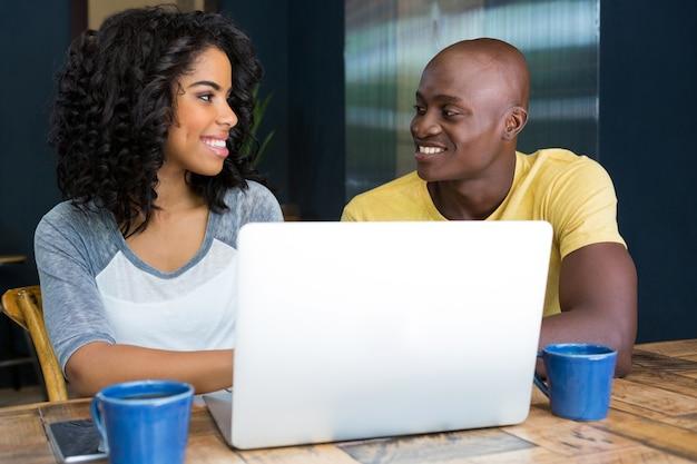 Smiling couple regardant les uns les autres avec un ordinateur portable sur la table dans un café