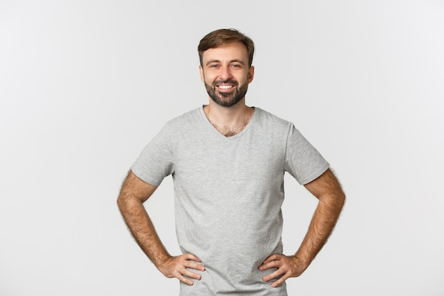 Smiling guy caucasien en chemise grise, l'air heureux et accompli