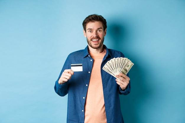 Smiling guy caucasien montrant une carte de crédit en plastique et de l'argent, l'air heureux, debout sur fond bleu.