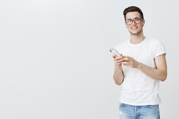 Smiling guy écoutant de la musique dans les écouteurs et tenant le smartphone