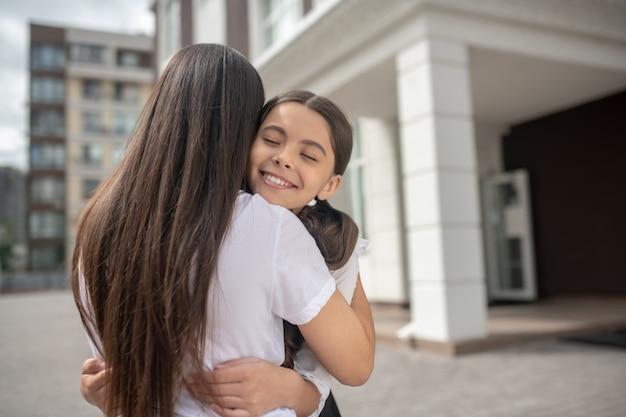 Smiling happy écolière fille aux yeux fermés serrant maman aux cheveux longs près de l'école matin ensoleillé