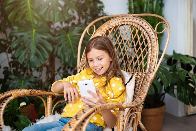 Smiling kid girl communique en ligne assis sur une chaise berçante à la maison, restez à la maison