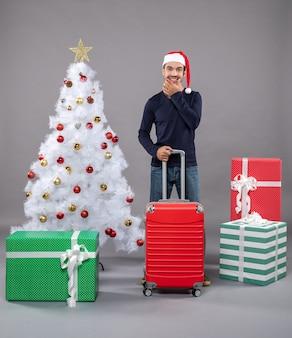 Smiling man holding red valise près de l'arbre de noël blanc avec des jouets de noël colorés sur
