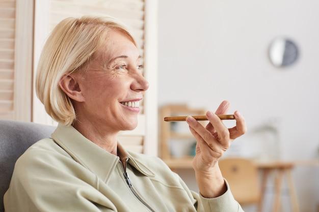 Smiling mature woman holding mobile phone et l'enregistrement d'un message assis sur le canapé à la maison