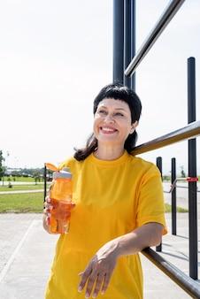 Smiling senior woman eau potable après l'entraînement à l'extérieur sur le terrain de sport
