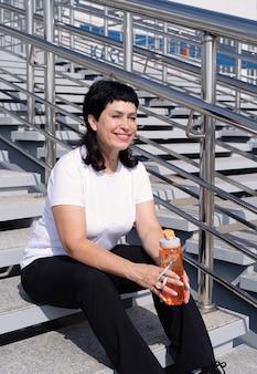 Smiling senior woman eau potable après l'entraînement à l'extérieur